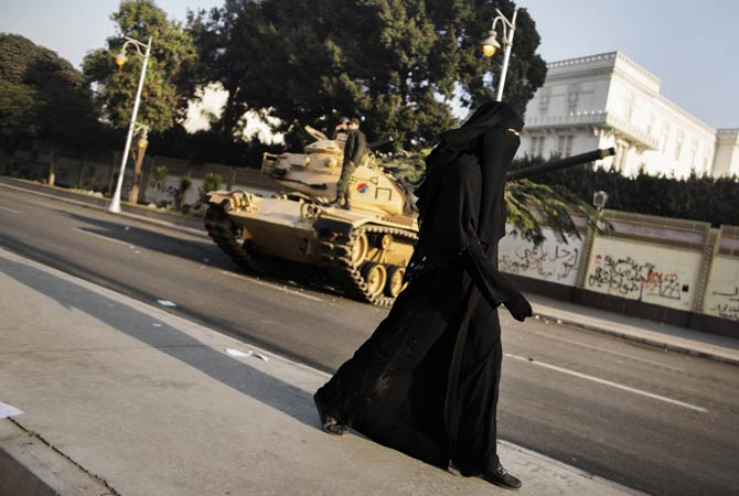 An fully-veiled Egyptian woman walks past an army tank parked outside the presidential palace in Cairo.