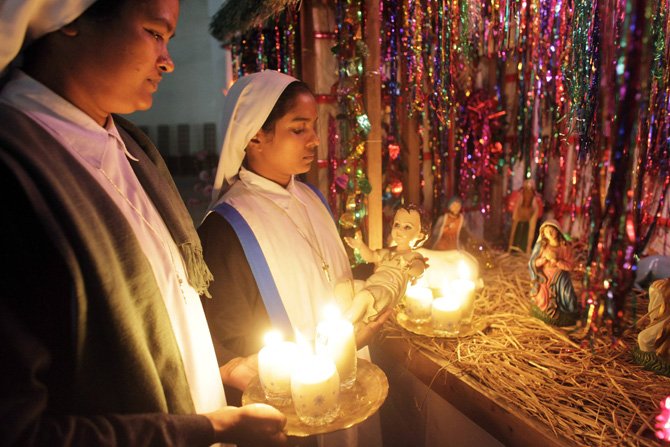 Nuns decorate an altar of Holy Rosary Church with statues representing the nativity scene on Christmas eve in Dhaka December 24, 2012. ? Photo by Reuters
