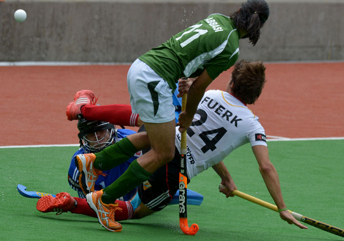 Shakeel Abbasi of Pakistan (C) gets the ball past Benedikt Fuerk and Felix Reuss of Germany during the first quarter final at the Men's Hockey Champions Trophy in Melbourne on December 6, 2012. Pakistan beat the number one ranked Germany 2-1. ? Photo by AFP