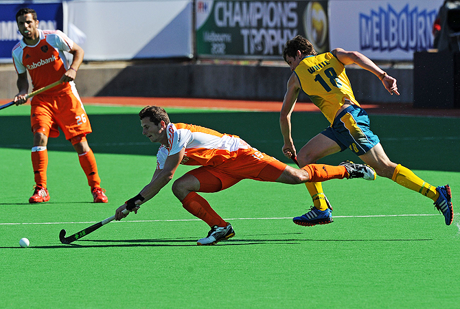 Sander Baart of the Netherlands (C) dives for the ball intercepting a pass to Tristan White of Australia (R).