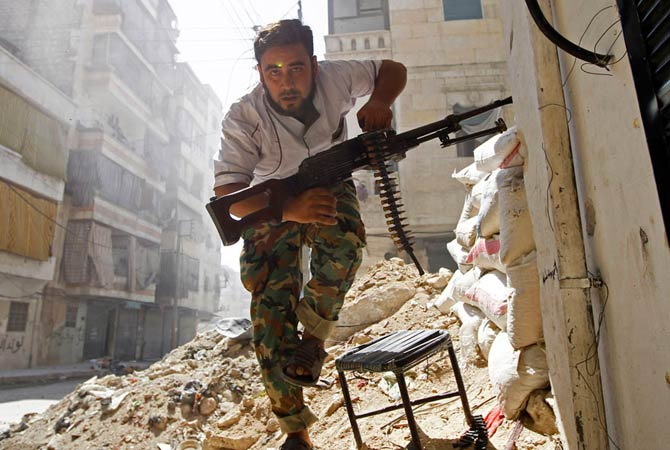 A Free Syrian Army fighter takes cover during clashes with Syrian Army in the Salaheddine neighborhood of central Aleppo August 7, 2012.