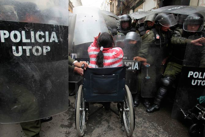 A physically disabled woman on her wheelchair clashes with riot police in the centre of La Paz, February 23, 2012. Hundreds of physically disabled people arrived in La Paz after completing a protest march of some 1600 km (994 miles) over a hundred days to demand that Bolivia's government offer support in the form of 3000 bolivianos ($434) payment to each physically disabled Bolivian, according to local media.
