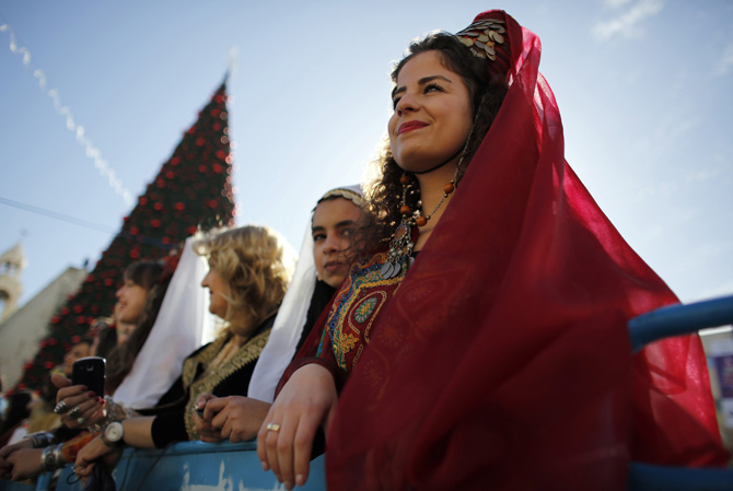 A Palestinian women dressed in traditional costume watches a Christmas parade outside the Church of Nativity in the West Bank town of Bethlehem December 24, 2012.  ? Photo by Reuters