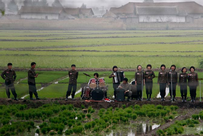 A music group performs on a path amid fields to greet the farmers at Hwanggumpyong Island, near the North Korean town of Sinuiju and the Chinese border city of Dandong June 6, 2012.