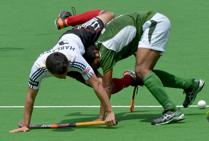 Shafqat Rasool of Pakistan pushes through Patrick Hablawetz of Germany during the first quarter final at the Men's Hockey Champions Trophy in Melbourne on December 6, 2012. Pakistan beat the number one 1 ranked Germany 2-1. ? Photo by AFP PHOTO/Paul CROCK