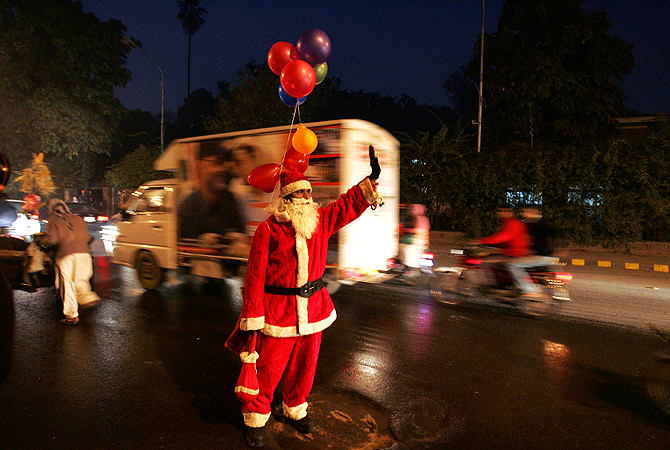 A man dressed as Santa Claus waves to people in street on the eve of Christmas celebrations in Lahore December 24, 2012. ? Reuters Photo