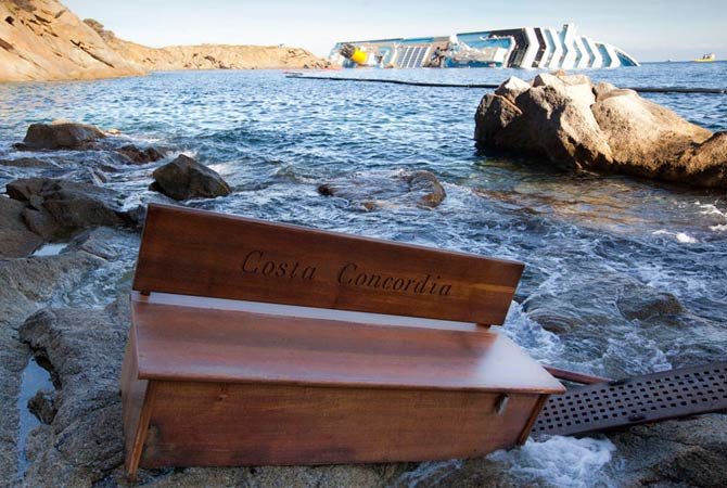 A bench engraved with the name of the grounded Costa Concordia cruise ship (seen at rear) is seen washed up on the shore of Giglio island, January 20, 2012.