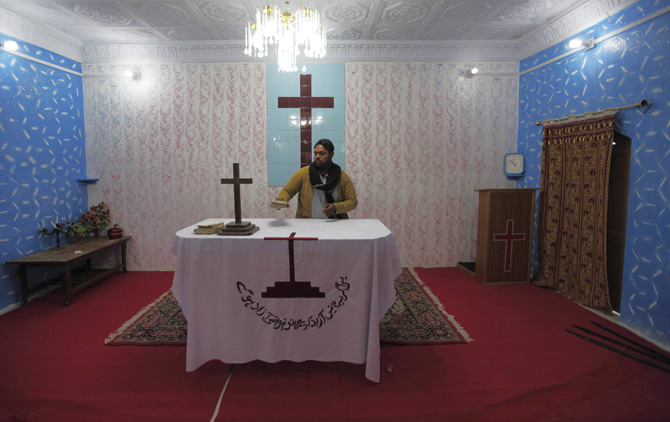 "A Pakistani altar boy tidies up the Communion table at a church in South Waziristan November 28, 2012.This Christmas, pastor Nazir Alam will stoke up a fire, lay a fresh cloth on the altar and welcome parishioners as they arrive at his church in Waziristan, a Pakistani tribal area known as an al-Qaeda haven. The words on the table reads in Urdu, ""If your son will free you then you are really free."" Picture taken on November 28, 2012. ? Photo by Reuters"