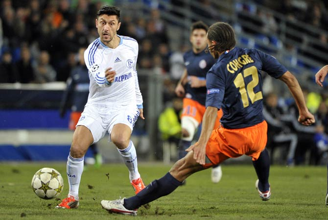 Schalke's Romanian forward Ciprian Marica kicks a ball next to Montpellier's french defender Daniel Congre during the UEFA Champions League football match Montpellier Herault SC vs FC Schalke 04 on December 4, 2012 at the La Mosson stadium in Montpellier.