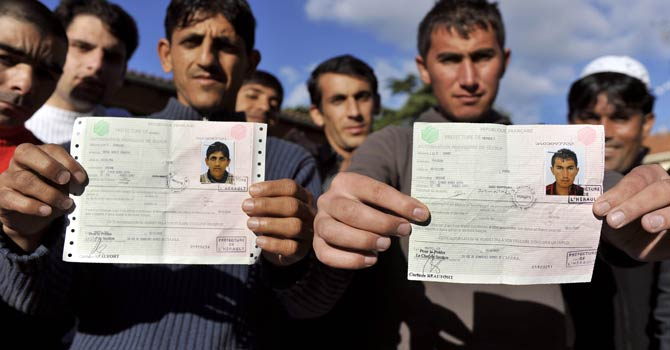 In this photograph taken on November 8, 2009, Afghan Fraidoun (R) and Abdoul (L) pose with their temporary resident permit in Nimes, southern France. – File photo by AFP