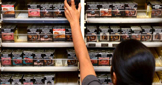 An employee in a bookshop adjusts packaged cigarettes which have to be sold in identical olive-brown packets bearing the same typeface and largely covered with graphic health warnings, with the same style of writing so the only identifier of a brand will be the name on the packet, in Sydney. – Photo by AFP