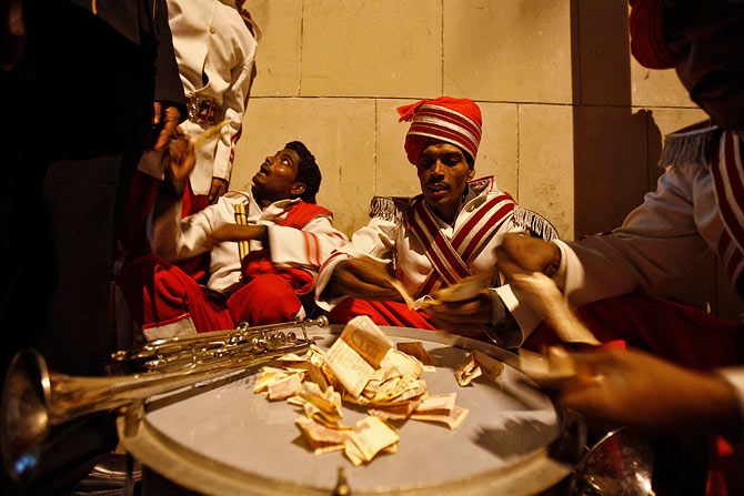 Members of a brass band distribute money they got as tip from the relatives and friends of a groom.