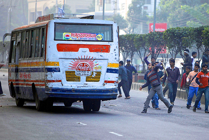 Bangladesh's largest Islamic party Jamaat-e-Islami activists damage a bus during a nationwide strike on the outskirts of Dhaka, Bangladesh.?Photo by AP