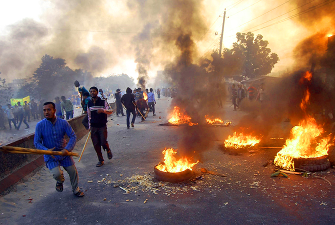 Bangladesh's largest Islamic party Jamaat-e-Islami activists block a road with burning tires during a nationwide strike on the outskirts of Dhaka, Bangladesh.?Photo by AP