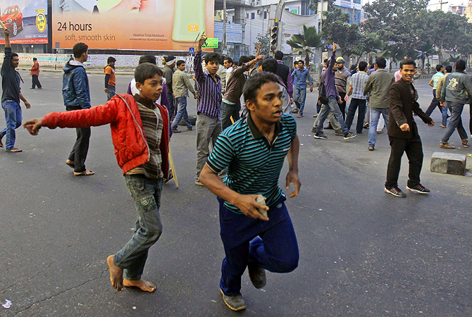 Activists of Bangladesh's largest Islamic party Jamaat-e-Islami shout slogans and run with stones in hand during a nationwide strike in Dhaka, Bangladesh.?Photo by AP