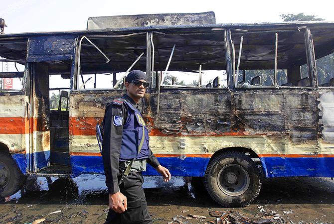 A member of the Rapid Action Battalion (RAB) inspects a burnt bus after activists of Bangladesh's Jamaat-e-Islami party set fire to it during a strike in Dhaka.?Photo by Reuters