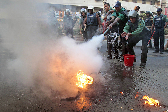Bangladeshi policemen douse flames on a tire set on fire during a nationwide strike by the country's largest Islamic party Jamaat-e-Islami in Dhaka, Bangladesh.?Photo by AP