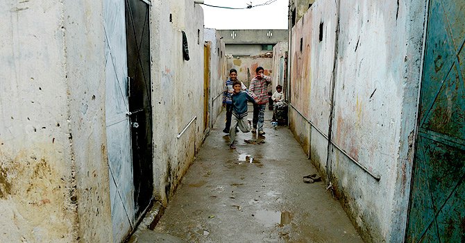 Pakistani Christian children stand outside their homes in the run-down area of Mehrabad on the outskirts of Islamabad.