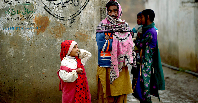 Pakistani Christians stand outside their homes in the run-down area of Mehrabad on the outskirts of Islamabad.