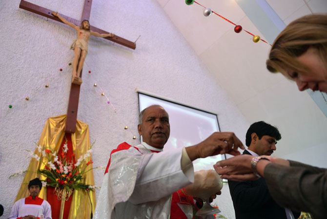 A Christian takes communion during Christmas mass at the Fatima Church in Islamabad on December 25, 2012.