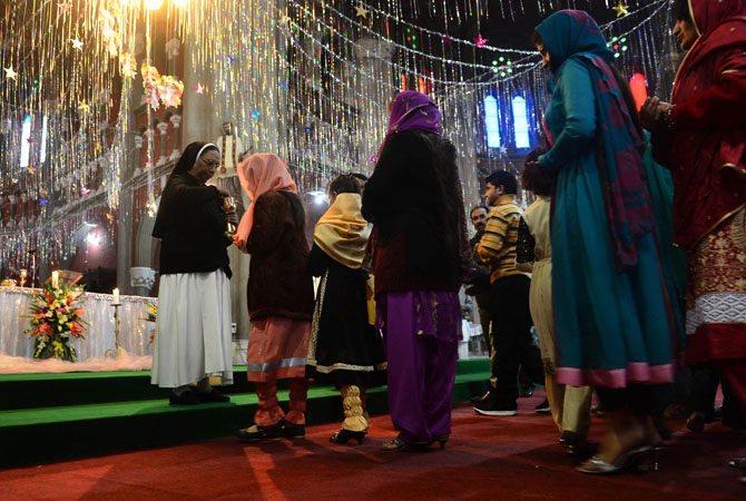 Pakistani Christians take communion during a Christmas mass at Saint Antony's Church in Lahore on December 25, 2012.