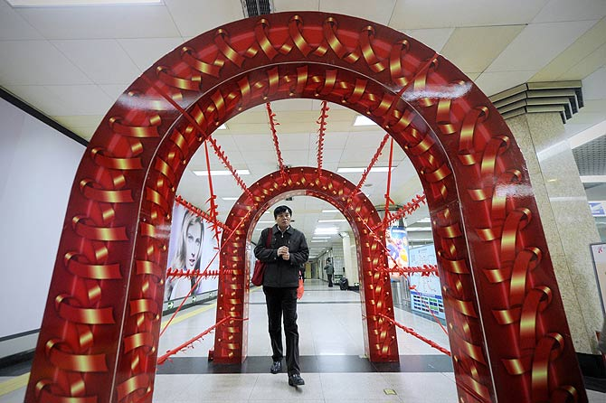 A man walks through an arch decorated with illustrations of AIDS awareness ribbons during a AIDS awareness event at a subway station on World AIDS Day in Beijing.? Photo by AFP