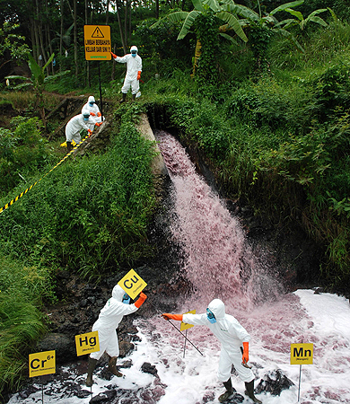 Greenpeace activists wearing protective suits mark waste discharge from an industrial firm containing highly toxic chemicals being dumped into the Cihaur river which flows into Citarum River in Padalarang district in West Java province on December 11, 2012. The environmental group is campaigning to eliminate hazardous chemicals in Indonesian rivers. – Photo by AFP