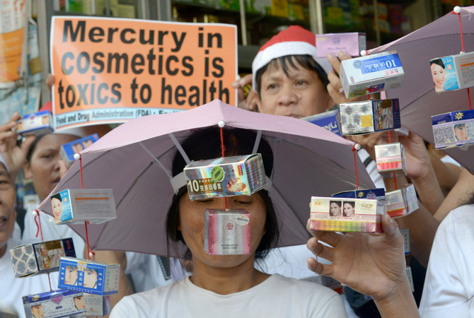 Protestors rally in front of a drug store as they hold allegedly mercury tainted cosmetics in Manila on December 11, 2012. The group urge local traders to stop selling mercury tainted cosmetics that are harmful to people and the environment. – Photo by AFP