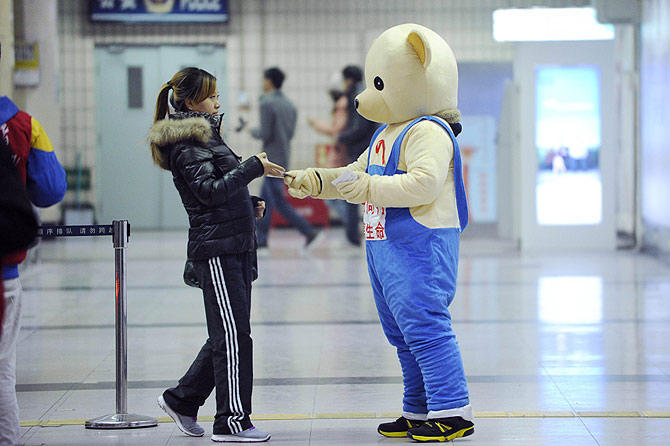 A volunteer dressed as a bear (R) hands out leaflets with an AIDS awareness message at a subway station. ? Photo by AFP