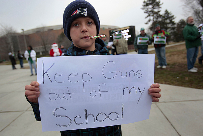 Jack Gilchrist, 10, chews on a candy cane as he holds a 'Keep guns out of my school' sign as he and his mother protest outside the Breslin student center in East Lansing, Michigan.?Photo by Reuters