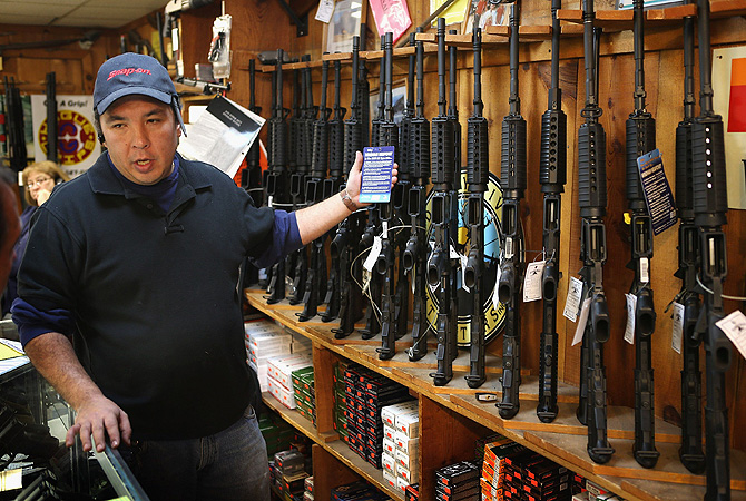 Jason Zielinski shows a customer a selection of AR-15 style rifles being offered for sale at Freddie Bear Sports sporting goods store in Tinley Park, Illinois. About 47 per cent of Americans own guns.?Photo by AFP