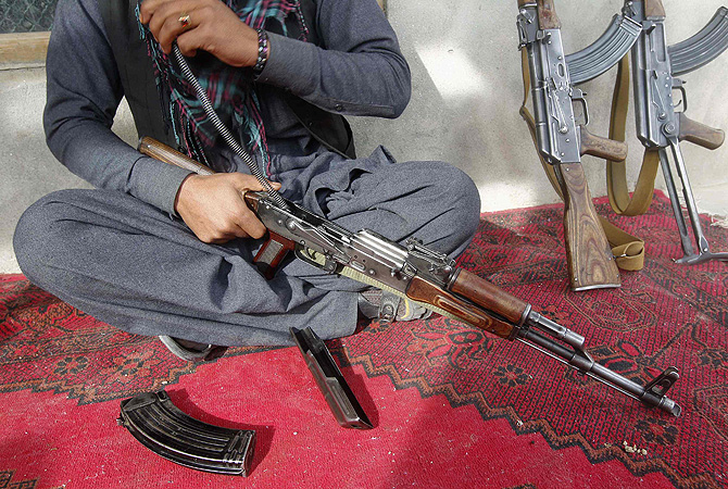 A weapons dealer cleans his AK-47 assault rifle at his house in Laghman province. Arms purchases are soaring in Afghanistan, along with the price of weapons, a sign that many Afghans fear a return of the Taliban, civil war or rising lawlessness.?Photo by Reuters
