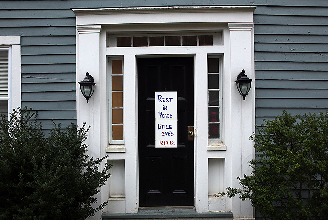 A message is left on a door in remembrance of those killed down the street from the Sandy Hook School in Newtown, Connecticut. Twenty-six people were shot dead, including twenty children, after a gunman identified as Adam Lanza opened fire at Sandy Hook Elementary School.?Photo by AFP