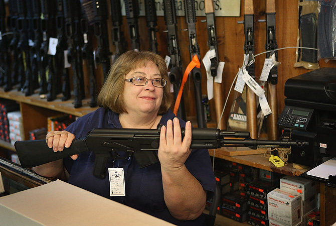 Cindy Sparr boxes a AK-47 style rifle purchased by a customer at Freddie Bear Sports sporting goods store in Tinley Park, Illinois. Americans purchased a record number of guns in 2012 and gun makers have reported a record high in demand.?Photo by AFP