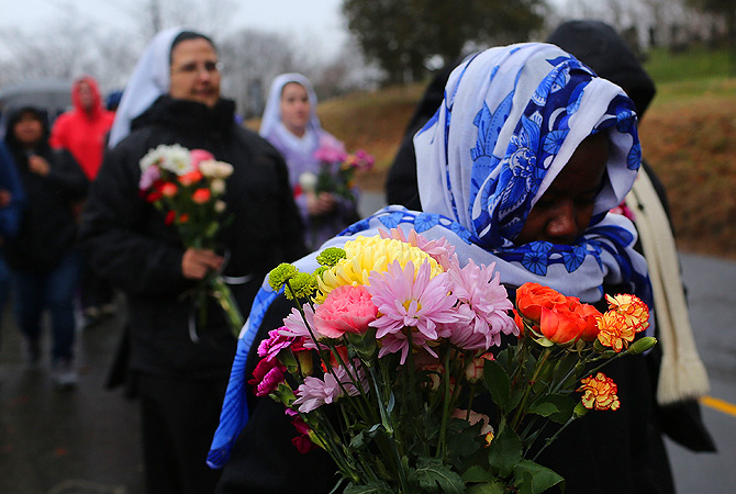 Members of Sisters of Christian Charity walk to lay flowers in front of the Sandy Hook School in Newtown, Connecticut.?Photo by AFP