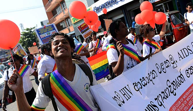 Sri Lankan activists hold a placard marked with symbolic red ribbons, take part in a gathering to mark World AIDS Day in Colombo. Some 1,161 HIV positive cases have been identified in the country between 1987 and the end of September 2011. ? Photo by AFP