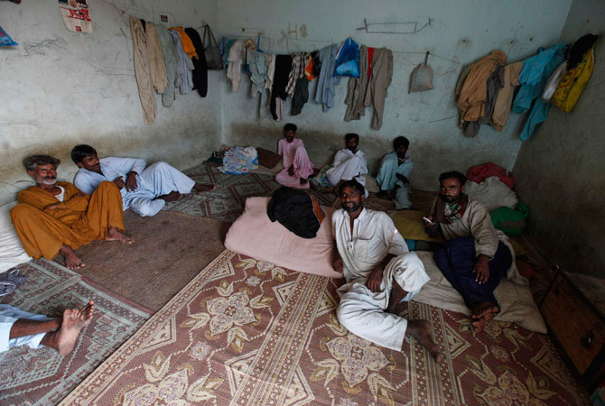 Fishermen rest in their room near the Ibrahim Hyderi fish harbour, some 17 km (11 miles) from Karachi December 7, 2012.