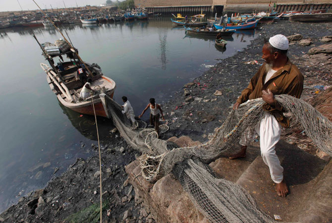 Men load fish nets onto a boat before they depart for a catch at the Ibrahim Hyderi fish harbour, some 17 km (11 miles) from Karachi December 7, 2012.