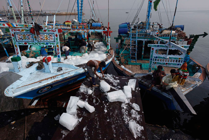 A labourer loads ice blocks onto a fishing boat before it departs for a catch in the Arabian Sea from the Ibrahim Hyderi fish harbour, some 17 km (11 miles) from Karachi December 7, 2012.