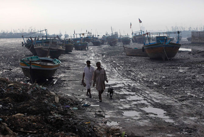 Fishermen walk past standing boats in Ibrahim Hyderi fish harbour, some 17 km (11 miles) from Karachi December 7, 2012.