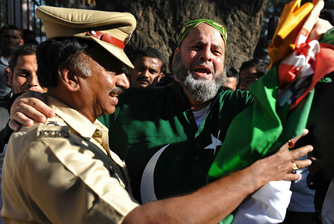 Mohammed Bashir, a 60-year old US-based Pakistani cricket fan, jokingly hugs an Indian police officer outside the M. Chinnaswamy Stadium on the eve of the India-Pakistan cricket series in Bangalore on December 24, 2012. Few Pakistani fans had made it to Bangalore on December 24 but one who had travelled from the United States said that it was too much to expect from cricket to serve as a propeller for diplomacy every time the teams played.