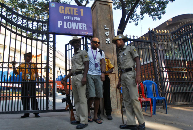 Private security men and Indian police personnel guard the main entrance of Chinnaswamy Stadium, the venue of first Twenty20 cricket match between India and Pakistan, in Bangalore, India, Monday, Dec. 24, 2012. The Pakistan cricket team is touring India for a short series, the first between the neighbors in five years which features two Twenty20 and three One Day International matches beginning at Bangalore on Dec. 25.