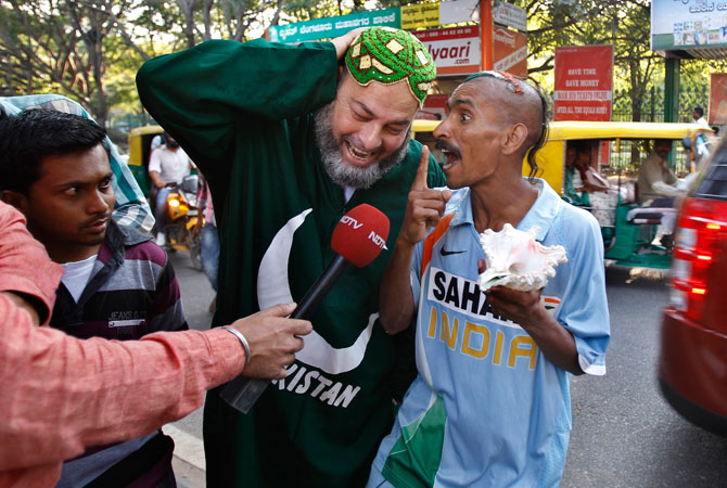 Pakistan cricket fan, Mohammad Bashir, second left, of Chicago, reacts as Indian fan Sudhir Kumar, right, shouts slogans while talking to a television reporter in front of the Chinnaswamy Stadium, the venue of first Twenty20 cricket match between India and Pakistan, in Bangalore, India, Monday, Dec. 24, 2012.