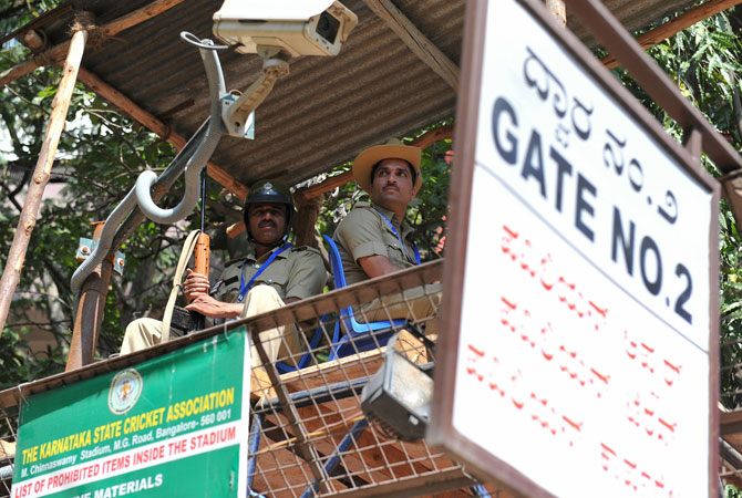 Indian policemen look on from a tower at an entrance to The M. Chinnaswamy Stadium in Bangalore on December 25, 2012.
