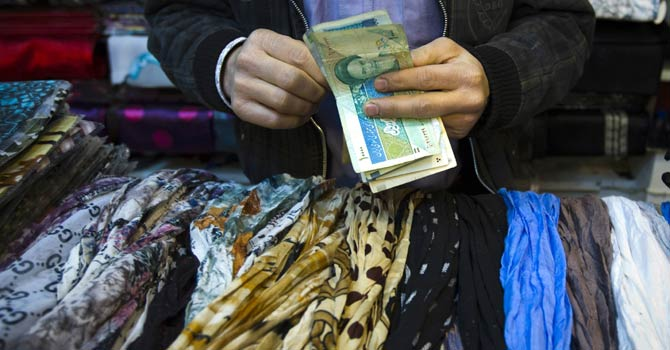 A shopkeeper counts Iranian bank notes at his shop in a bazaar in Tehran in this Feb 25, 2012 file photo. Iranian share prices have rallied 40 per cent in the past four months, at odds with the country's deteriorating economic fundamentals under the weight of sanctions and raising the risk of a stock market bubble, analysts say. - Reuters