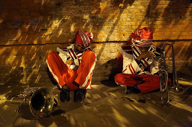Members of a brass band rest against a wall as they wait to perform.