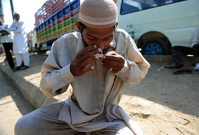 A Pakistani drug addict inhales heroin on the roadside in Karachi. Pakistani cleric Abdul Khaliq Faridi used to think HIV/AIDS was a mortal sin. But today, he educates thousands about a disease on the rise in the deeply conservative Muslim country. ? Photo by AFP