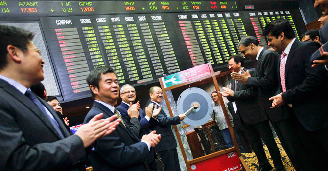 Gao Xiqing, President of China Investment Corporation (CIC) smiles as he holds a mallet to hit the ceremonial gong during his visit to the Karachi's Stock Exchange December 3, 2012. - Photo by Reuters