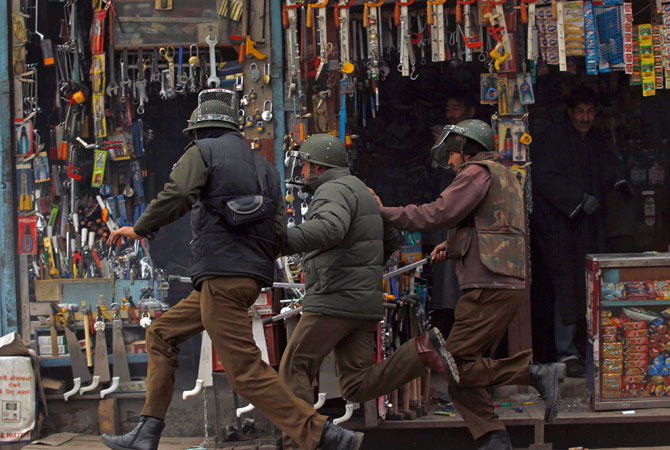 Indian policemen run for cover past shops selling tools during clashes with supporters (unseen) of Jammu Kashmir Liberation Front (JKLF) in Srinagar December 7, 2012.