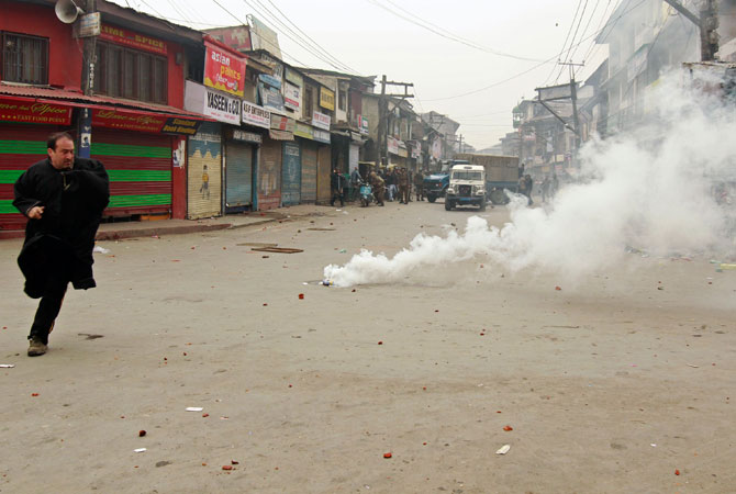 A supporter of the Jammu Kashmir Liberation Front (JKLF) runs from tear gas during clashes with police in Srinagar December 7, 2012.